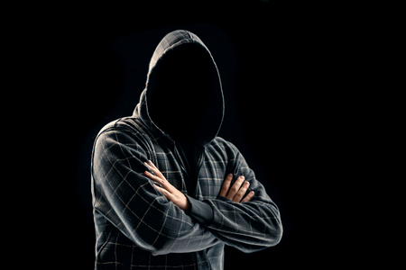 Silhouette of a man in a hood on a black background, his face is not visible, he folded his arms over his chest. The concept of a criminal, incognito, mystery, secrecy, anonymity. Banco de Imagens