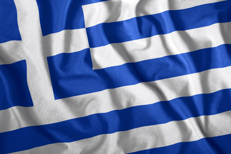 The Greece flag flies in the wind. Colorful national flag of the Greece. Patriotism, patriotic symbol. Stock Photo