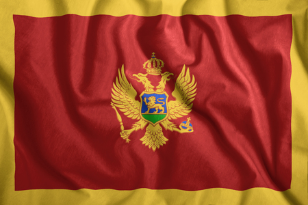 The Montenegro flag flies in the wind. Colorful national flag of the Montenegro. Patriotism, patriotic symbol.