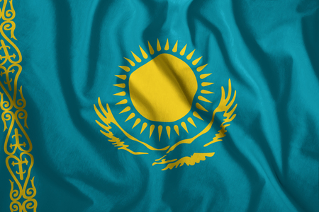 The Kazakh flag flutters in the wind. Colorful, national flag of Kazakhstan. Patriotism, a patriotic symbol. Stock Photo