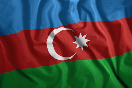 The Azerbaijani flag is flying in the wind. Colorful, national flag of Azerbaijan. Patriotism, a patriotic symbol. Stock Photo