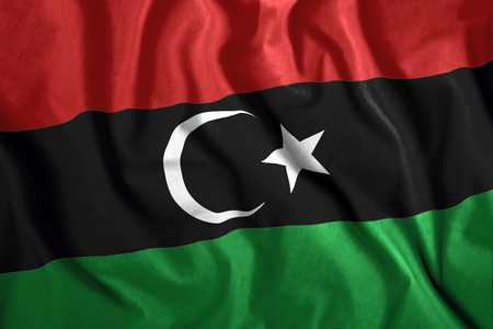 The Libyan flag flies in the wind. Colorful national flag of Libya. Patriotism, patriotic symbol. Stock Photo