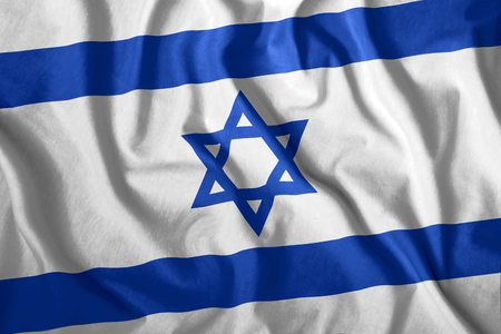 The Israeli flag is flying in the wind. Colorful national flag of Israel. Patriotism, patriotic symbol. Stock Photo