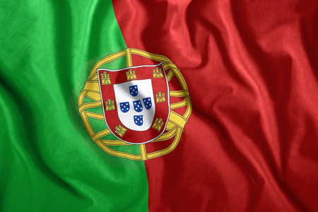 The Portugal flag flies in the wind. Colorful national flag of the Portugal. Patriotism, patriotic symbol.