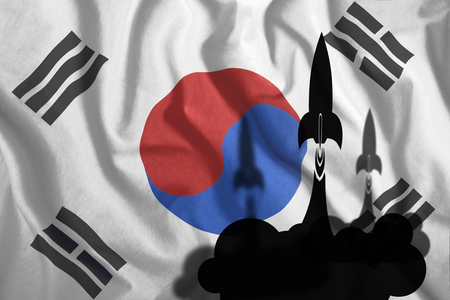 Flying rockets against the background of the South Korean flag, fluttering in the wind. Colorful national flag of South Korea. Patriotism, patriotic symbol, war, conflict.