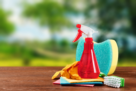 Image with various tools for cleaning the premises and cleaning agents on a blurred natural background. The concept of cleaning the premises, cleanliness.