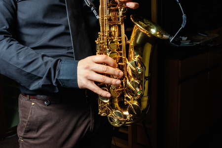 Saxophone Player hands Saxophonist playing jazz music. Alto sax musical instrument closeup Фото со стока