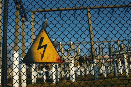 A sign of cautiously electricity, A warning sign over explains the dangers of nearby power lines. Banco de Imagens
