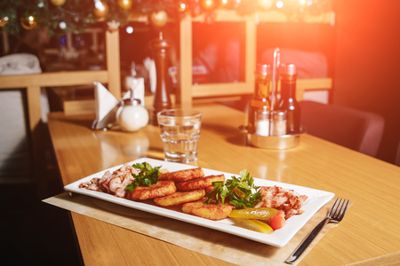 Potato pancakes with bacon on a white rectangular plate on a table in a restaurant. Table setting at the restaurant.