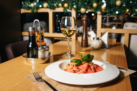 Pasta tagliatelle with tomatoes on a white plate on a table in a restaurant. Table setting at the restaurant. Imagens