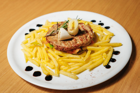 Pork chop, pasta, leeks, rosemary on a white plate. Stock Photo