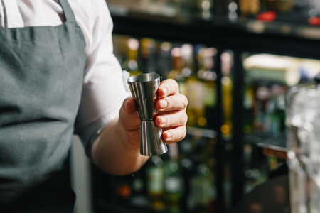 Male hands of the bartender close-up, makes a cocktail on the bar, glasses with ice.