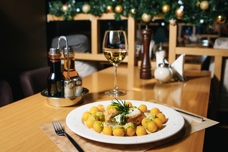 Chicken fillet with spinach and gnocchi on a white plate on a table in a restaurant. Table setting at the restaurant.