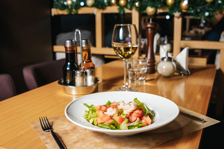 Salad of shrimp, avocado, tomato, lettuce and lemon. A white plate, a table in the restaurant.
