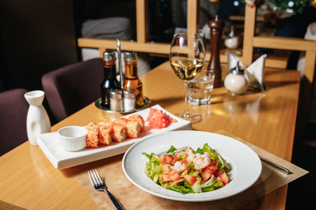Salad of shrimp, avocado, tomato, lettuce and lemon. A white plate, a table in the restaurant. Sushi Sesame Maki.
