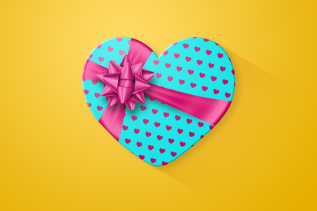 Turquoise gift wrapping, a box in the shape of a heart with a festive pink bow, on a bright yellow background. Romance, Valentines Day, love.