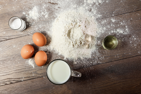 Top view of the egg, flour, a glass of fresh milk, cooking dough on the background of a wooden table. Flat lay