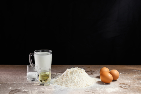 Flour and eggs, cooking dough. The recipe for cooking pizza, pasta, bread. House cooking from the chef. Dark background.