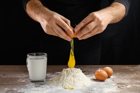 Hands of the cook close-up, breaks the egg into flour, a glass of fresh milk, cooking dough on a dark background. Reklamní fotografie