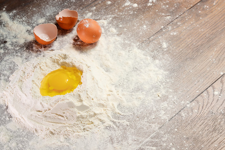 The top view of an egg, beaten into flour, cooking dough against the background of a wooden table. Flat lay, copy space.