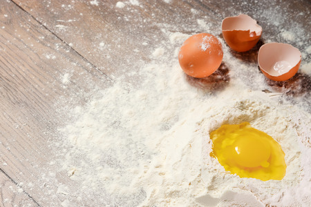 The top view of an egg, beaten into flour, cooking dough against the background of a wooden table.