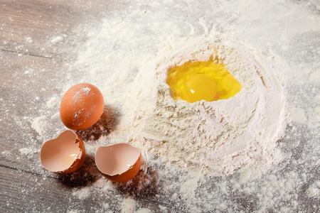 The top view of an egg, beaten into flour, cooking dough against the background of a wooden table. Flat lay