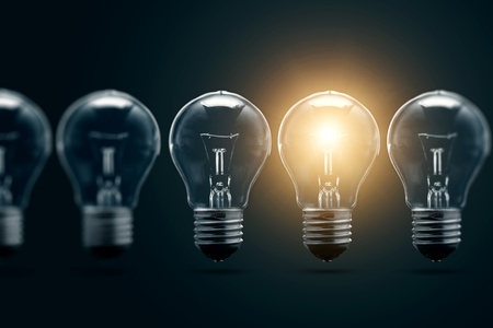 A series of electric light bulbs, only one glows, against a dark background. The concept of several attempts, one successful. A successful idea. Stock Photo