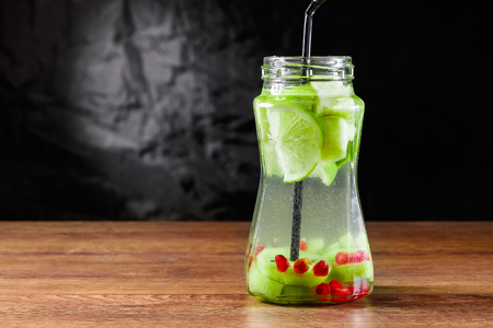 Refreshing drink from kiwi, green apple, lime, mint and pomegranate on a wooden table. The concept of a healthy diet, detox.