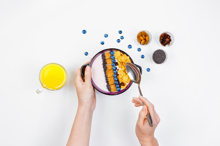 Breakfast, female hands holding a spoon over a bowl with homemade yogurt and cornflakes, and fresh blueberries, a glass of orange juice on a white background, top view, flat lay. Concept of healthy food, healthy food, detox. Copy Space