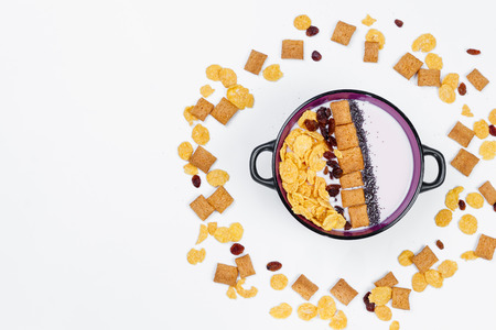 Morning breakfast. Bowl with homemade yogurt and cornflakes, raisins, almonds on white background, top view, flat lay. Concept of healthy food, healthy food, detox. Copy Space 版權商用圖片