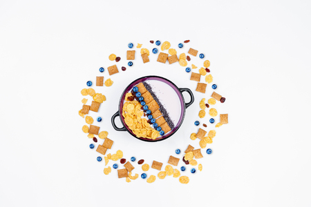 Breakfast, bowl with homemade yogurt and cornflakes and fresh blueberries on white background, top view, flat lay. Concept of healthy food, healthy food, detox. Copy Space