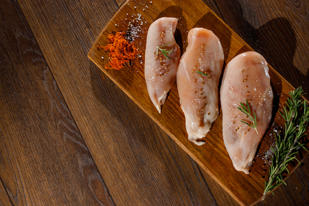 Raw chicken breast, pepper, rosemary on a cutting board, on a wooden background, top view. Raw chicken meat for cooking. Delicious balanced nutrition concept. Copy space Zdjęcie Seryjne