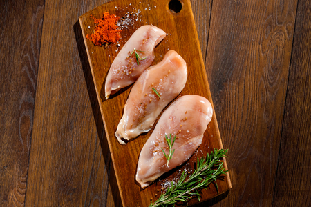 Raw, chicken fillet on a cutting board, a kitchen board, rosemary, pepper, salt, seasoning. The concept of a recipe for cooking chicken.