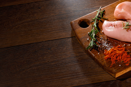 Raw chicken breast, pepper, rosemary on a cutting board, on a wooden background, close-up. Raw chicken meat for cooking. Delicious balanced nutrition concept. Copy space