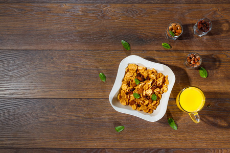 Morning breakfast, corn flakes, raisins, almonds, orange juice, top view, on a dark wooden background, flat lay. The concept of healthy, proper nutrition, ditox.