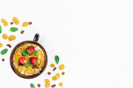 Cereal, morning breakfast, corn flakes, raisins, almonds, mint leaves, strawberry, top view, white background, flat lay. The concept of healthy, proper nutrition, ditox. Banco de Imagens