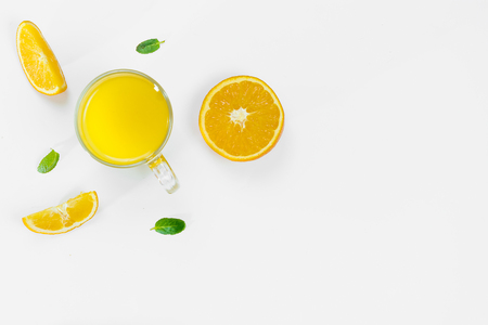Cut orange, slices, mint leaves, orange juice in a glass top view on a white background, flat lay. The concept of healthy, proper nutrition, ditox.
