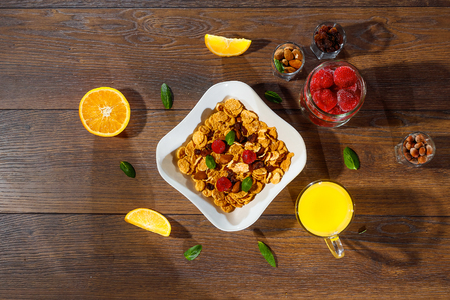 Cereal, morning breakfast, corn flakes, raisins, almonds, mint leaves, orange juice, strawberry, top view, on a dark wooden background, flat lay. The concept of healthy, proper nutrition, ditox. 스톡 콘텐츠