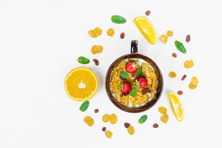 Cereal, morning breakfast, corn flakes, raisins, almonds, mint leaves, orange juice, strawberry, top view, white background, flat lay. The concept of healthy, proper nutrition, ditox.