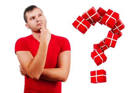 The question of what to present for the new year. A man in a red T-shirt on a white background, thought about the gift.