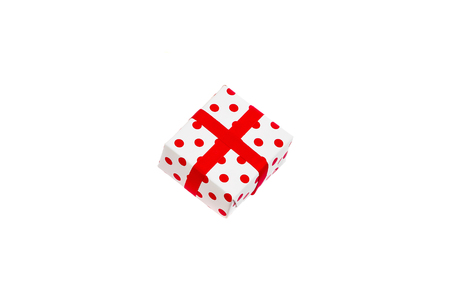 White-red New Year's gift in polka-dot, isolated on white background.