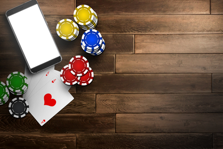 Online casino, mobile casino, top view of a mobile phone, chips cards on a wooden background. Gambling games.