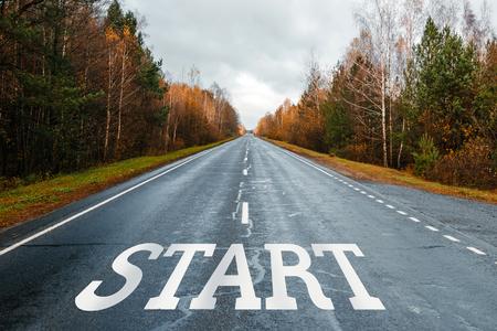 L'inscription START sur la route, l'autoroute dans la forêt d'automne, mélèze, pin, paysage, jour. Le concept du début du chemin.
