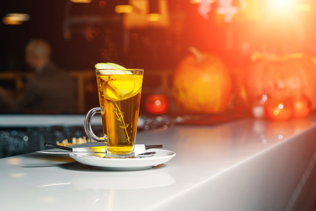 Green tea with apple slices in a glass cup on a white bar counter Imagens