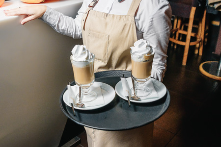 Cold coffee with whipped milk and caramel ice cream in high glasses on a tray in the hands of the waiter, selective focus