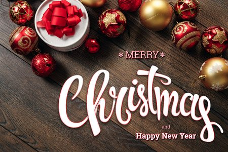 The inscription of Merry Christmas and Happy New Year, decorations and gifts on a wooden brown table. Christmas card, holiday background. Mixed media.