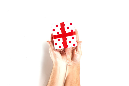 Male hands holding gift, red white gift box with ribbon, isolated on white background, top view. Isolate. New Year, Christmas, birthday.