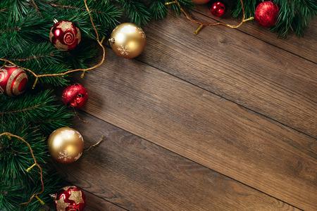 Ornamenti di Natale e rami di pino su un tavolo di legno. Fondo di natale di feste. Copia spazio per testo o design. Vista dall'alto.