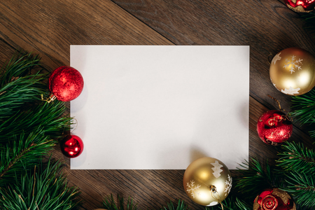 A frame of pine branches and Christmas decorations and A4 sheet of white paper on a wooden table. Holidays christmas background. Copy space for text or design. View from above.