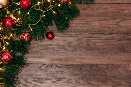 Christmas ornaments and pine branches on a wooden table. Holidays christmas background. Copy space for text or design. View from above.